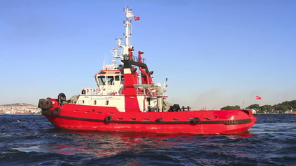 Pilotage service boat in front of harbor. Red tow boat