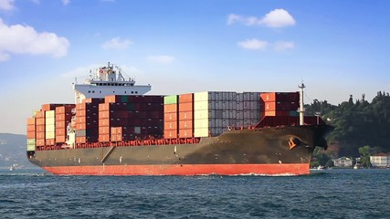 Cargo container ship sailing under clear blue sky