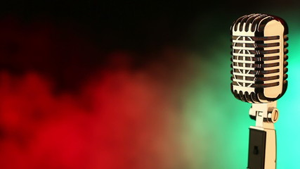 Vintage microphone on red and green smoke background