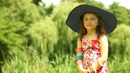 Little girl child kid putting on straw hat outdoor