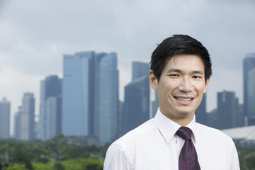 Happy asian business man in front of city.