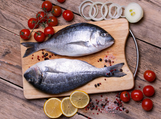 Two fresh gilt-head bream fish on cutting board with lemon,