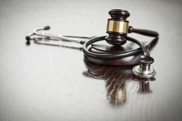 Gavel and Stethoscope on Reflective Table