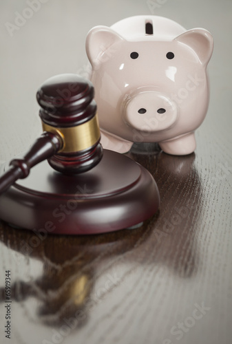 Gavel and Piggy Bank on Table Poster