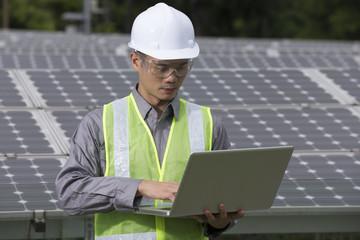 Asian engineers checking solar panel setup
