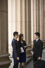 Asian business colleagues outside a Colonial building.