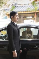 Asian chauffeur/businessman standing next to luxury car.
