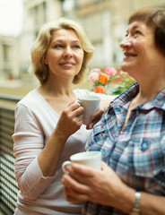 Two mature women drinking coffee