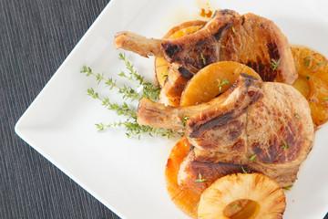 Pork ribs steak wtih pineapple slice on dish on black mat