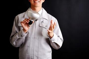 電球を持っている作業服の男性