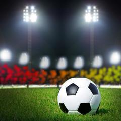 football on the grass field with stadium light