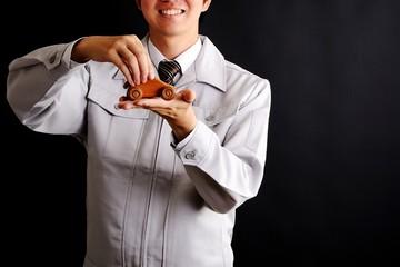 車の模型を持っている作業服の男性