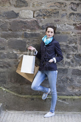 Young woman standing by a stone wall holding shopping bags.