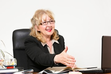 Smiling middle aged businesswoman, at the desk in office.