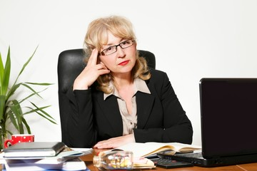 Middle aged businesswoman, at the desk in the office.