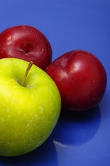 Plum fruit and green apple over blue background