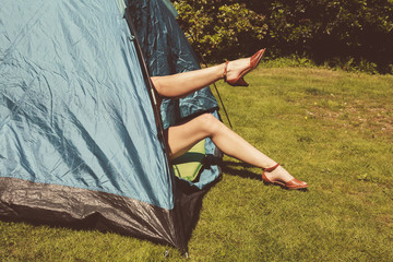 Young woman raising her legs from inside a tent