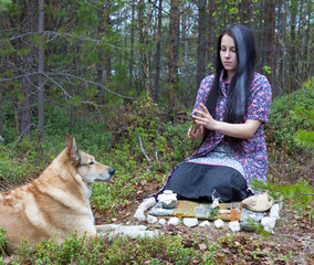 Girl witch conjures in the woods. Near a huge dog
