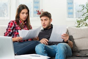 couple calculating their domestic bills at home