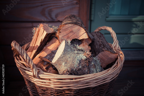 Basket of firewood on the porch - 65928759