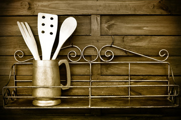 Kitchen cooking utensils on rustic kitchen wall