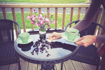 Woman setting table for tea outside