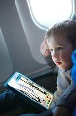 Little boy drawing on a tablet in an airplane