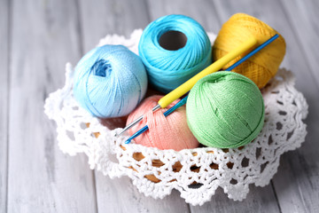 Colorful clews, napkin and crochet hook in wicker basket,