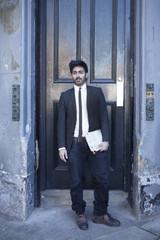 Portrait of Indian man standing in a doorway.