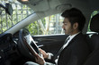 Indian businessman sitting in parked car using Tablet. - 65934311