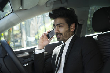 Indian businessman sitting in his car and talking on phone.