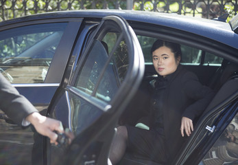 Asian businesswoman stepping out of limousine.