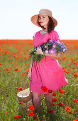Beautiful young woman holding wicker bag in poppy field