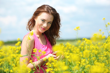 Beautiful young woman with cherries in field