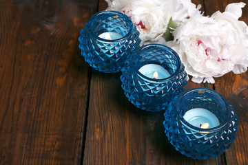 Glass candlesticks and flowers on color wooden background