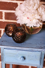 Glass candlesticks and flowers on stand, on bricks background