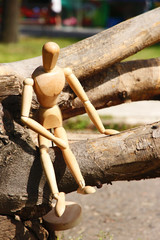 Wooden pose puppet sitting on wooden timber, outdoors