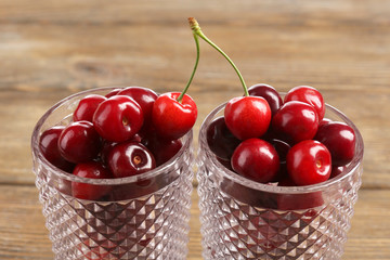 Sweet cherries in glasses on wooden table