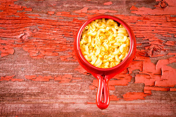 Kids cheese macaroni in clay pot on rustic table
