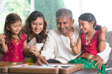 Happy Indian family playing carrom game