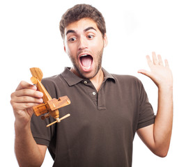 young man playing with a wooden plane