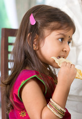 Indian girl eating snack.