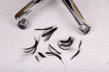 Cut hair on the floor in hairdressing salon, close up