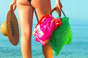 Close up of a woman by the sea,holding beach amenities.