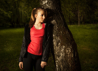 Teenage girl leaning on a tree