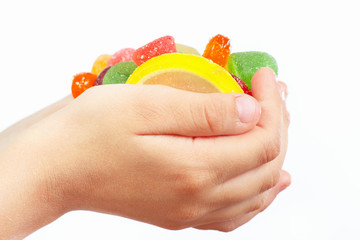 Child hands with colorful fruity sweets close up