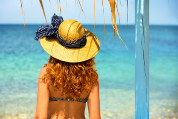 Young woman, wearing hat, looking at the beach.