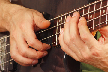 Hands of artist playing the bass guitar closeup