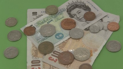 Sterling UK cash and coins rotating a green  background.