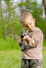 Cute boy aiming with machine gun